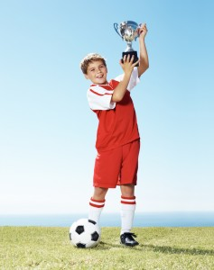 Kid holding a soccer trophy